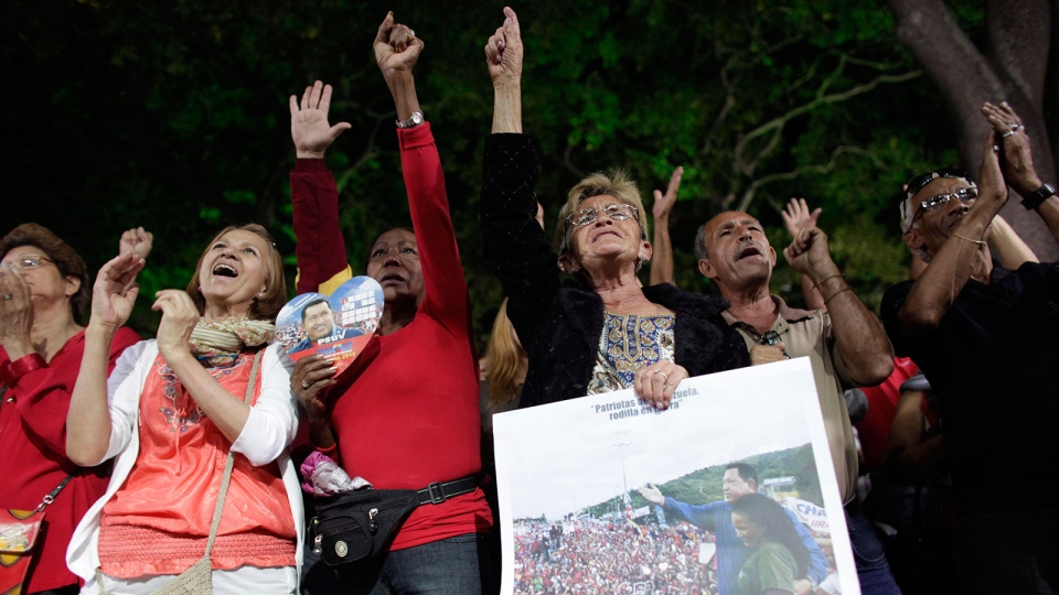 People, some of them holding an image of Venezuela's President Hugo Chavez, gather to pray for him at a church in Caracas, Venezuela, Monday, Dec. 31, 2012. (AP / Ariana Cubillos)