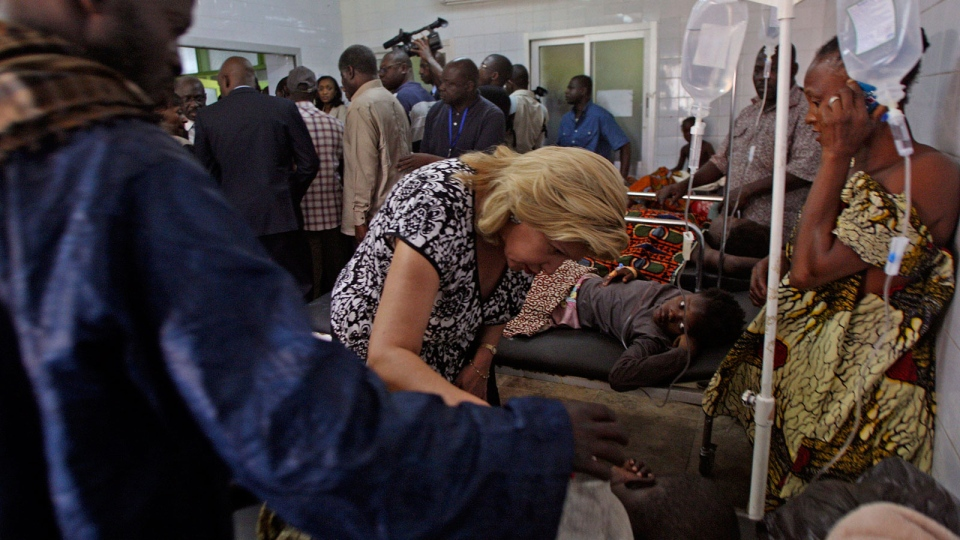 Ivory Coast First Lady Dominique Ouattara, centre left, speaks with a person injured in a stampede as they are treated at a hospital in Abidjan, Ivory Coast, Tuesday, Jan. 1 2013. (AP / Emanuel Ekra)