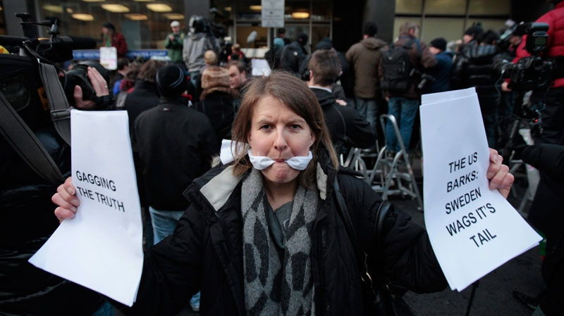 A supporter of Wikileaks founder Julian Assange, poses for members of the media outside the City of Westminster Magistrates Court in London where Julian Assange's case was heard, Tuesday, Dec. 7, 2010. (AP / Lefteris Pitarakis)