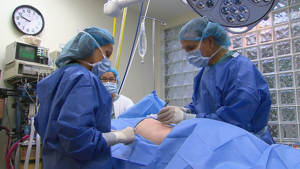 Doctors prepare to perform a liposuction treatment on Debra Seed. The extracted fat will be stored for later use.
