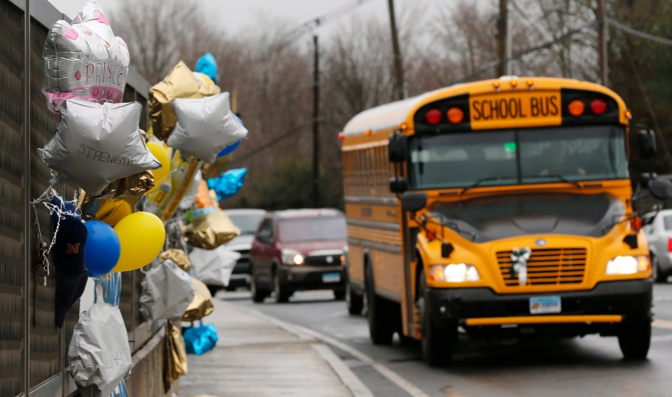 A school bus rolls toward a memorial for victims of the Sandy Hook Elementary School shooting, in Newtown, Conn., Dec. 18, 2012. (AP / Charles Krupa)