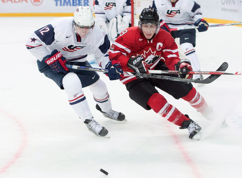 Team Canada forward Ryan Hugent-Hopkins, right, battles for the loose puck against Team USA forward Mario Lucia, left, during second period IIHF World Junior Championships hockey action in Ufa, Russia on Sunday, Dec. 30, 2012. (Nathan Denette / THE CANADIAN PRESS)