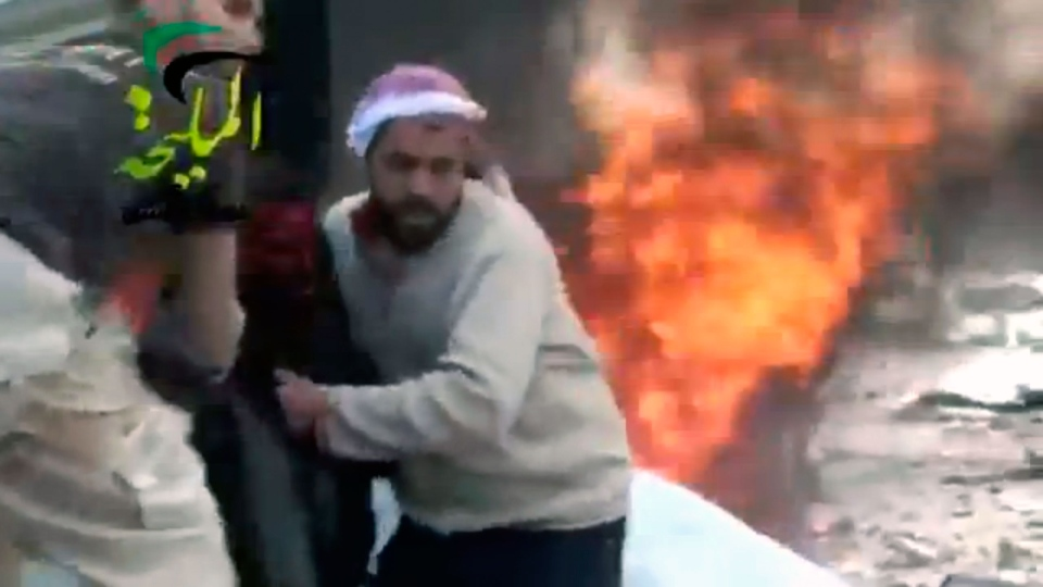 A wounded man is pulled from the site of a Syrian government airstrike on a gas station in the eastern Damascus suburb of Mleiha, Syria, Wednesday, Jan. 2, 2013. (Shaam News Network via AP video)