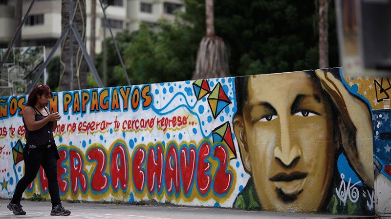 A woman walks past a mural of Venezuela's President Hugo Chavez in Caracas, Venezuela, Monday, Dec. 31, 2012. (AP / Ariana Cubillos)