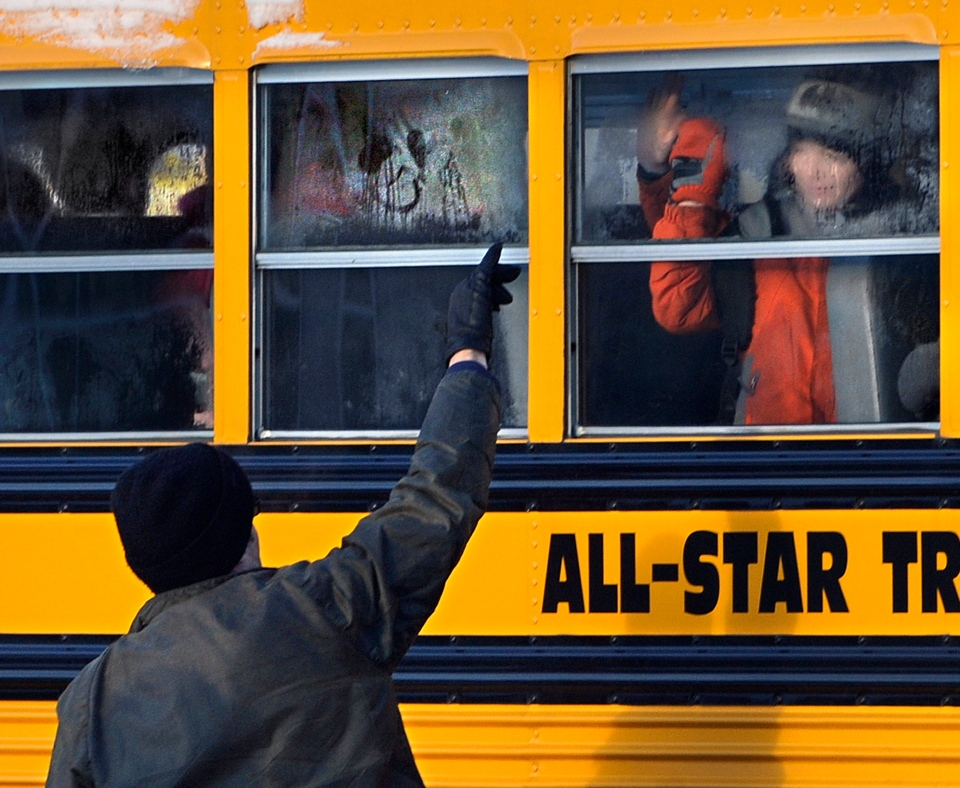 A man waves to a child on a bus on the first day of classes after the holiday break, in Newtown, Conn.,Wednesday, Jan. 2, 2013. (AP / Jessica Hill)