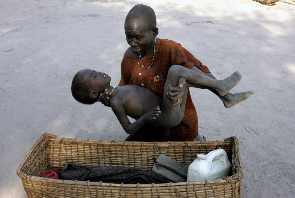 A mother gently places her son in a basket as she takes him to a Medecins Sans Frontieres clinic after he contracted malaria, in Lankien, Southern Sudan, on Dec. 21, 2005. (AP / Karel Prinsloo)