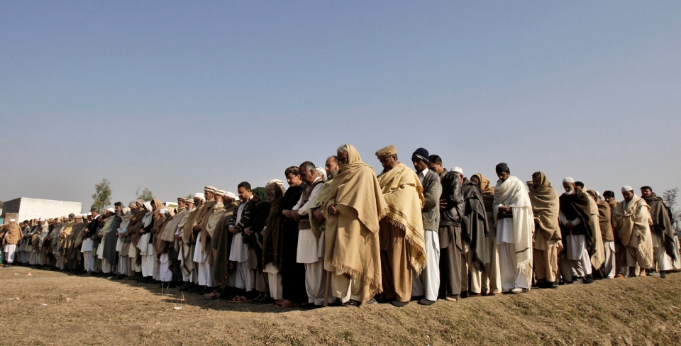 Pakistani relatives and mourners pray next to the body of aid worker Lubna Mahmoud during her funeral procession in Swabi, Pakistan, Wednesday, Jan. 2, 2013. (AP / Mohammad Sajjad)
