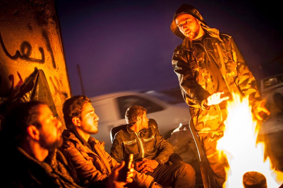 Syrian rebels gather around a fire as they plan patrols in the Saif al-Dawlah neighborhood of Aleppo, Syria, Wednesday, Jan. 2, 2013. (AP / Andoni Lubaki)