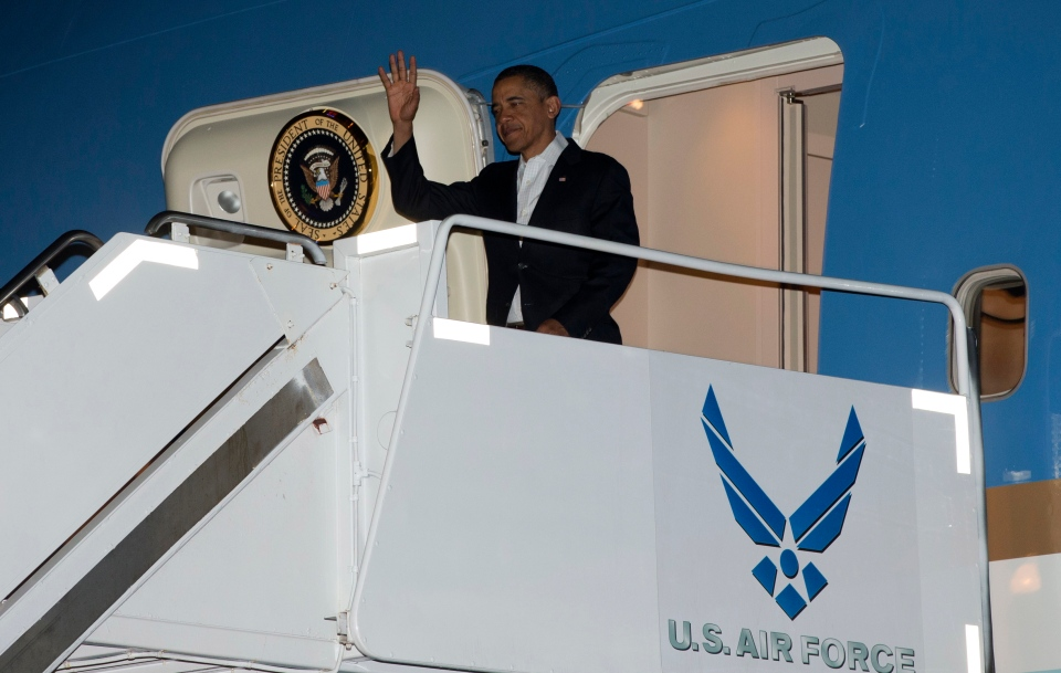 U.S. President Barack Obama waves as he gets off Air Force One upon his arrival at Joint Base Pearl Harbor-Hickam, Honolulu, Hawaii, Wednesday, Jan. 2, 2013.  (AP / Carolyn Kaster)