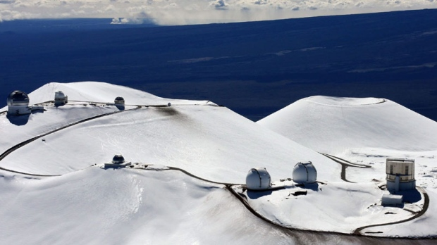 In this Jan. 6, 2009 file photo, the astronomy observatories atop the snow capped mountain of Mauna Kea are seen near Hilo, Hawaii. (AP Photo/Tim Wright)