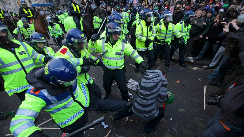 A police officer kicks a demonstrator during a protest against an increase in tuition fees on the edge of Parliament Square in London, Thursday, Dec. 9, 2010. (AP / Matt Dunham)
