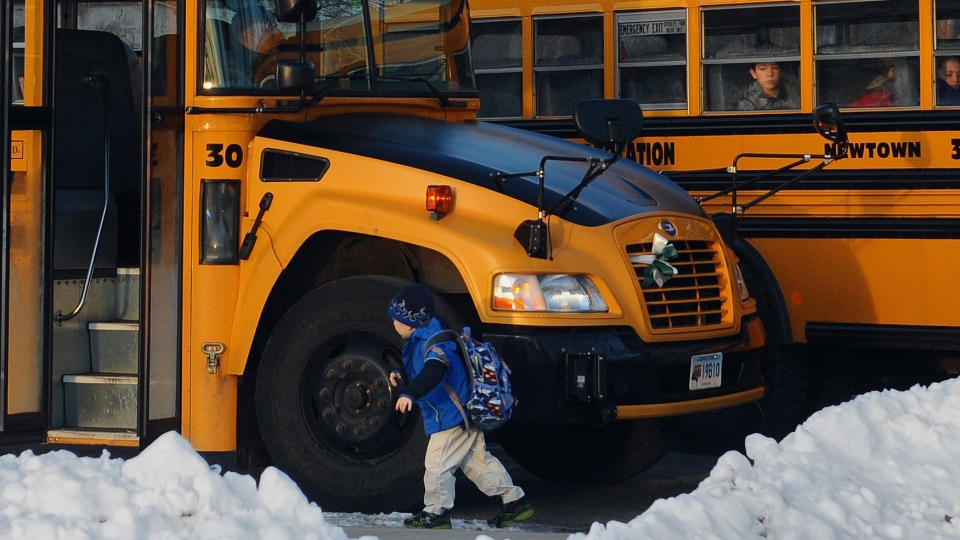 Children board a bus on the first day of classes after the holiday break, in Newtown, Conn., Wednesday, Jan. 2, 2013. (AP / Jessica Hill)