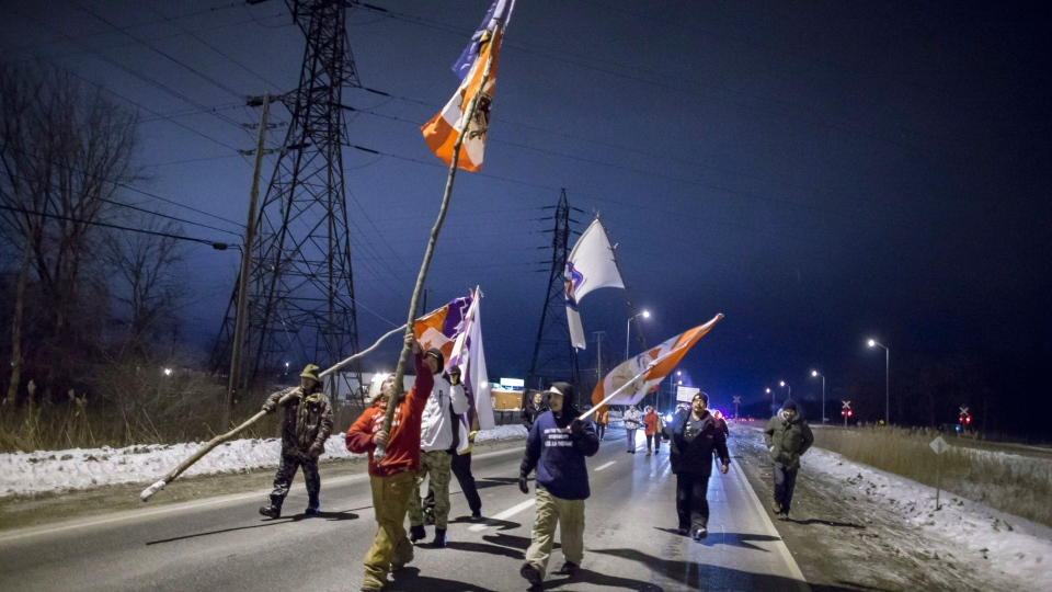 First Nations protesters march down Highway 40 after abandoning their blockade of the CN tracks when a court injunction ordered them to move, in Sarnia, Ont., Wednesday, Jan. 2, 2013. (Geoff Robins / THE CANADIAN PRESS)