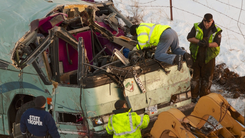 Workmen move the bus which plummeted 200 feet down an embankment in rural Eastern Oregon Sunday, killing nine and sending multiple to hospitals, Monday, Dec. 31, 2012. (The Oregonian, Randy L. Rasmussen)
