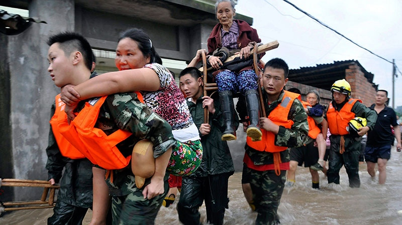 Rescue workers evacuate residents from flooded areas in Jianong town in Leshan in southwest China's Sichuan province on Sunday, July 18, 2010. (AP)