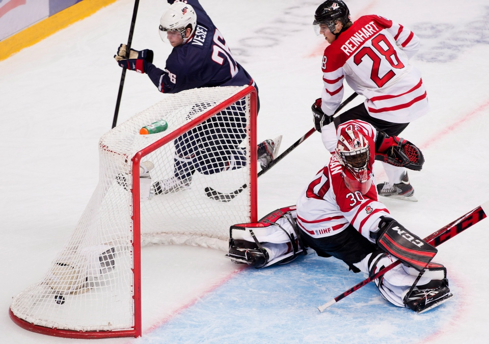 Canada goalie Malcolm Subban, front right, gets scored on by Team USA forward Jim Vessy, left, as Canada defenceman Griffin Reinhart (28) looks on during third period semi-final IIHF World Junior Championships hockey action in Ufa, Russia on Thursday, Jan. 3, 2013. (Nathan Denette / THE CANADIAN PRESS)