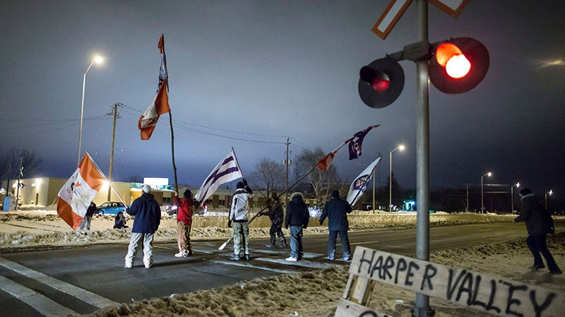 First Nations protesters march down the railway tracks after abandoning their blockade of the CN tracks in Sarnia, Ont., Wednesday, Jan. 2, 2013. (Geoff Robins / THE CANADIAN PRESS)
