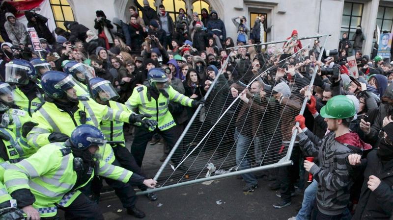Protesters and police officers clash during a demonstration against an increase in tuition fees, on the edge of Parliament Square in London, Thursday, Dec. 9, 2010. (AP / Matt Dunham)