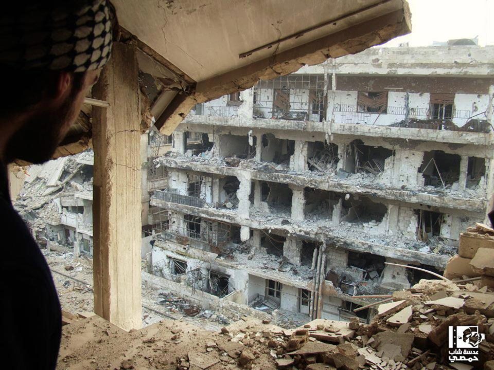 A Syrian man looks through a damaged building to another destroyed buildings, at al-Qossur neighborhood in Homs province, Syria, Thursday, Jan. 3, 2013. (AP / Lens Yong Homsi)