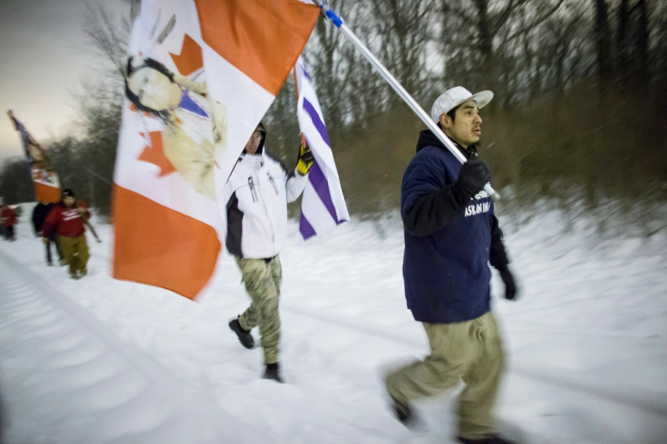 First Nations protesters march down the railway tracks after abandoning their blockade of the CN tracks in Sarnia, Ont., on Wednesday, Jan. 2, 2013. (Geoff Robins / THE CANADIAN PRESS)