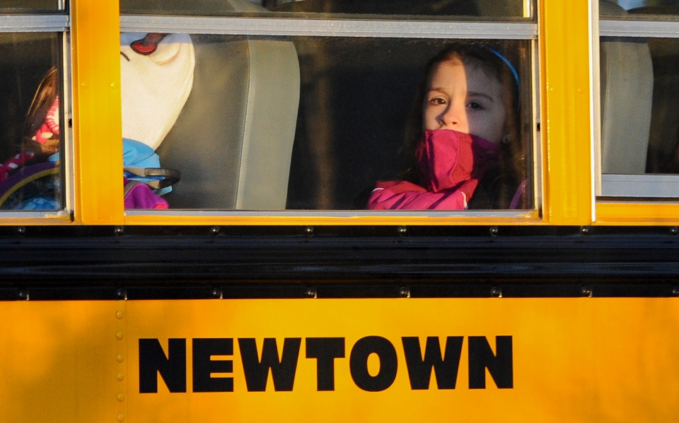 A girl sits on a Newtown bus leaving the new Sandy Hook Elementary School after the first day of classes in Monroe, Conn., Thursday, Jan. 3, 2013. (AP / Jessica Hill)