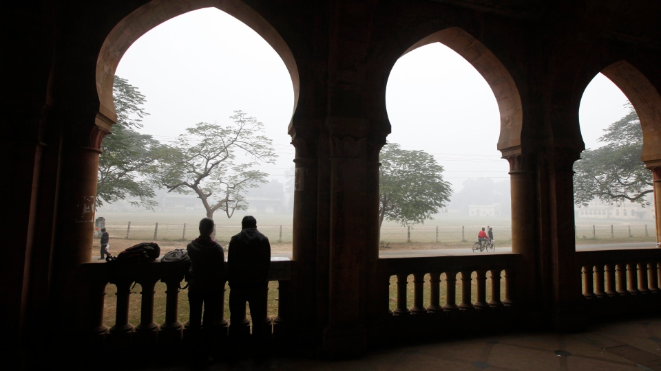Indian people watch from inside the Allahabad University campus on a cold and foggy morning in Allahabad, in the northern Indian state of Uttar Pradesh, India, Saturday, Dec. 22, 2012. (AP / Rajesh Kumar Singh)