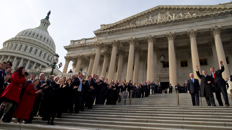 Members of Congress line the steps to the Senate door of the Capitol building on Capitol Hill in Washington, as Sen. Mark Kirk, R-Ill., second from right, accompanied by Sen. Joe Manchin, D-W.Va., right, and Vice President Joe Biden, waves as he walks the steps to mark his return to Congress, Thursday, Jan. 3, 2013. (AP / Evan Vucci)