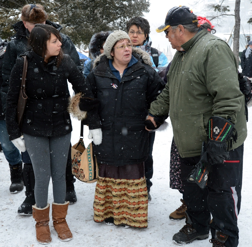 Attawapiskat Chief Theresa Spence is helped back to her teepee after greeting and welcoming supporters as they visit her on Victoria Island in Ottawa on Thursday, Jan. 3, 2013. (Sean Kilpatrick / THE CANADIAN PRESS)