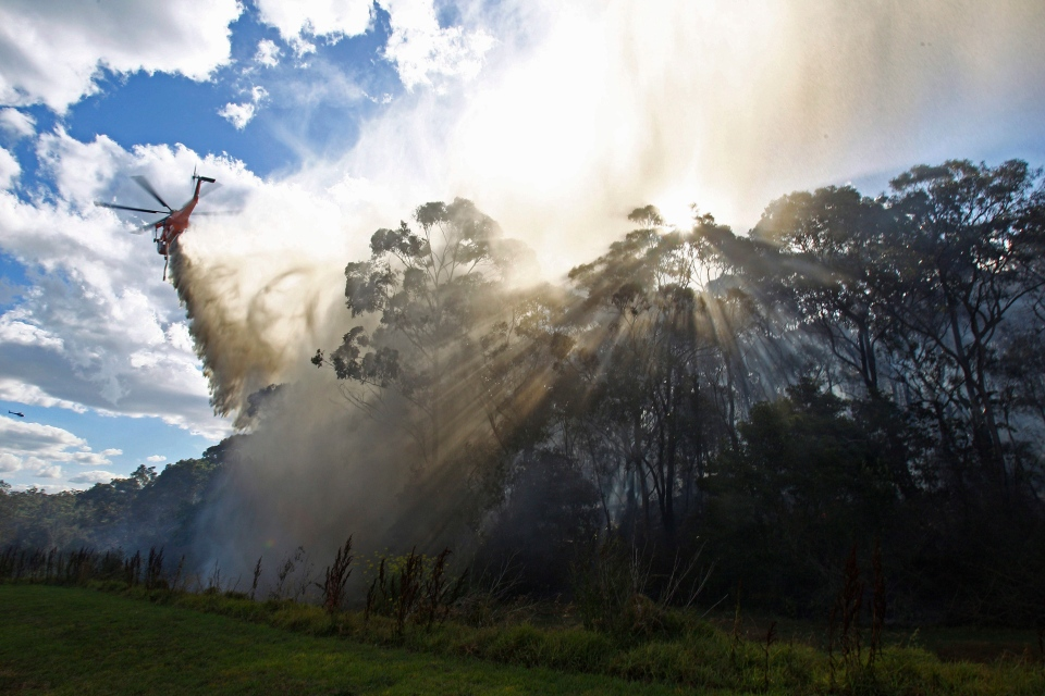 A helicopter drops water onto a smoldering fire in the Lane Cove National Park in Sydney, Wednesday, Dec. 5, 2012. Several firefighting aircraft contained the fire and no homes were lost. (Rick Rycroft/The Associated Press)
