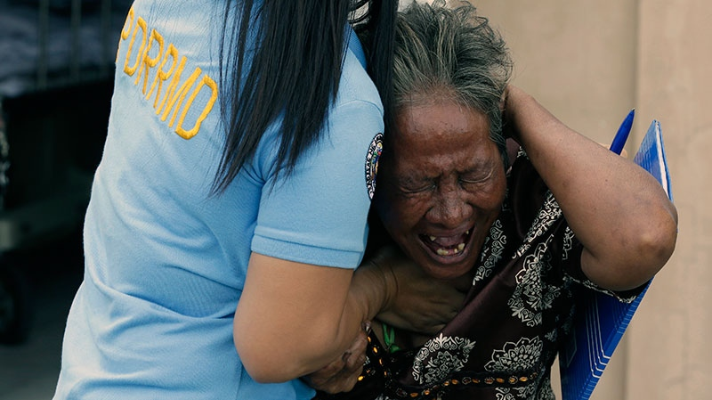 Aniolina Caimol, 63, the grandmother of shooting victim Micaela Caimol, 7, cries after viewing her grand daughter inside a morgue of a private hospital in Kawit township, Cavite province near Manila, Philippines, Friday, Jan. 4, 2013. (AP / Bullit Marquez)
