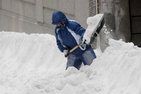 A man shovels snow in Montreal, on Sunday, March 9, 2008. (Graham Hughes / THE CANADIAN PRESS)