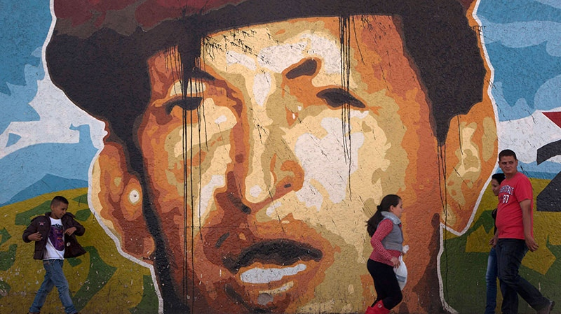 People walk a mural depicting Venezuela's President Hugo Chavez past in Caracas, Venezuela, Thursday, Jan. 3, 2013. (AP / Ariana Cubillos)