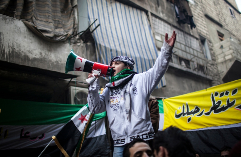 A child uses a megaphone to lead others in chanting Free Syrian Army slogans during a demonstration in the neighborhood of Bustan Al-Qasr, Aleppo, Syria, Friday, Jan. 4, 2013. (AP Photo/Andoni Lubaki)