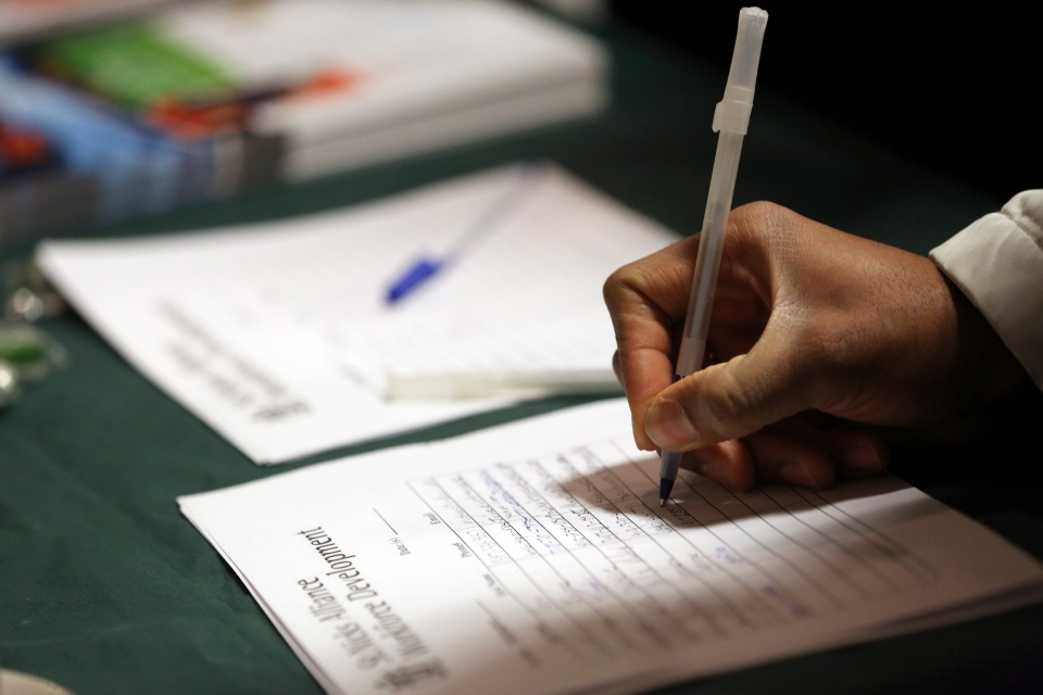 A job seeker leaves his contact information with a potential employer during a job fair in this December 2012 file photo. (AP / Mary Altaffer)
