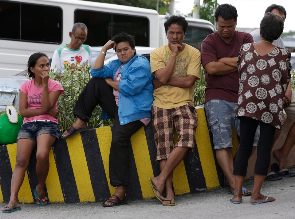 Relatives of shooting victims wait outside a hospital following a shooting rampage by a man later identified as Ronald Bae in Kawit township, Cavite province 16 kilometers south of Manila, Philippines Friday Jan. 4, 2013. (AP / Bullit Marquez)
