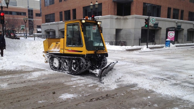 A small snowplow pushes snow in Montreal nearly a