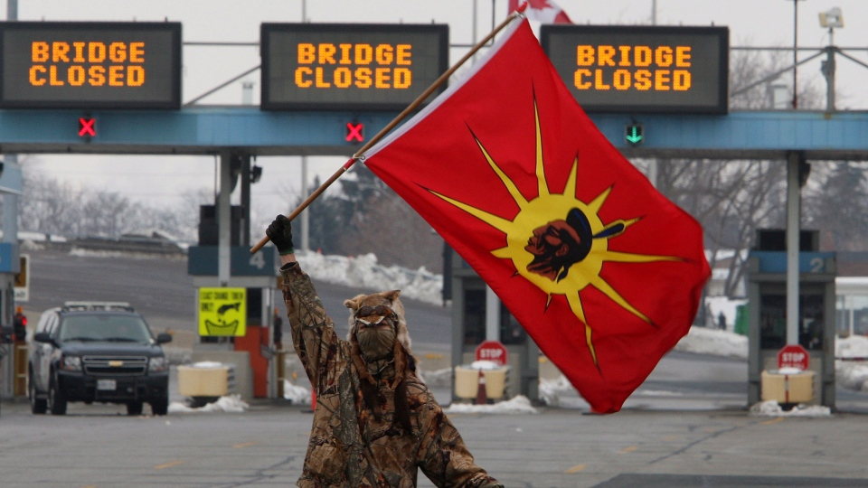 A man waves a flags as Aboriginal protesters and supporters in the Idle No More movement block the Blue Water Bridge border crossing to the United States in Sarnia, Ont. on Saturday, January 5, 2013. (Dave Chidley / THE CANADIAN PRESS)