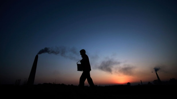 A boy walks past a brick factory on the outskirts of Jammu, India, Saturday, Dec. 11, 2010. After two decades of unbridled development, India is now the world's third-largest greenhouse gas emitter. (AP / Channi Anand)