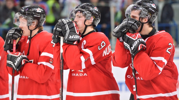 Canada captain Ryan Nugent-Hopkins, centre, hangs his head with teammates Morgan Rielly, left,and Phillip Danault after losing to Russia during overtime bronze medal hockey action at the IIHF World Junior Championships in Ufa, Russia, on Saturday, Jan. 5, 2013. (Nathan Denette / THE CANADIAN PRESS)