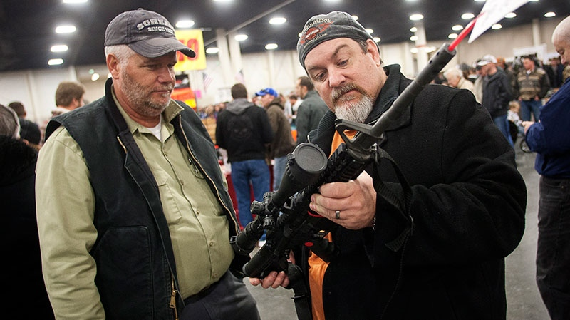 Gun owners discuss a potential sale of an AR-15, one of the most popular and controversial weapons, during the 2013 Rocky Mountain Gun Show at the South Towne Expo Center in Sandy, Utah Saturday, Jan. 5, 2013. (AP / The Deseret News, Ben Brewer)