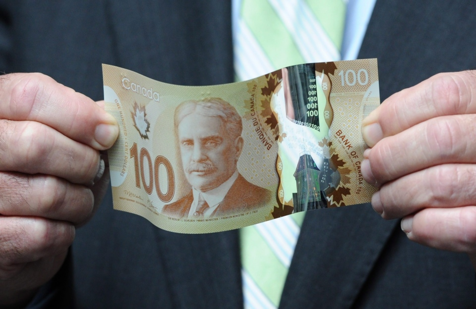Finance Minister Jim Flaherty holds a new polymer-based $100 bill as he takes part in the unveiling of the new polymer bank notes at the Bank of Canada in Ottawa on Monday, June 20, 2011. (Sean Kilpatrick / THE CANADIAN PRESS)