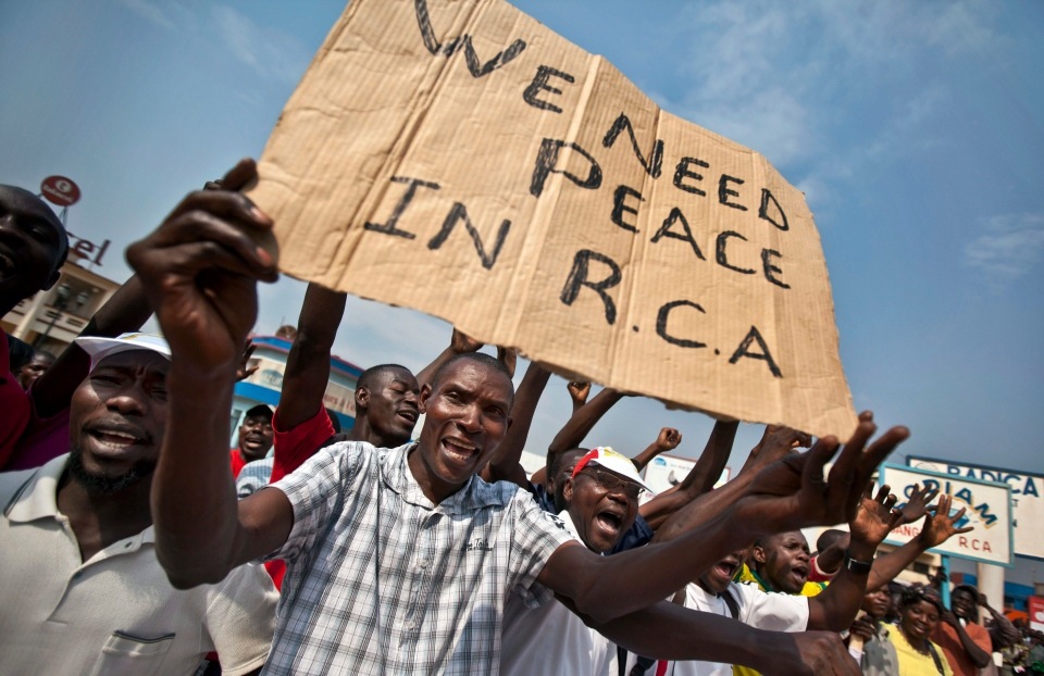 Several hundred protesting merchants, one holding a placard using the French acronym of the country's name, hold a demonstration calling for peace as negotiators prepare for talks with rebels from the north, in downtown Bangui, Central African Republic Saturday, Jan. 5, 2013. (AP / Ben Curtis)
