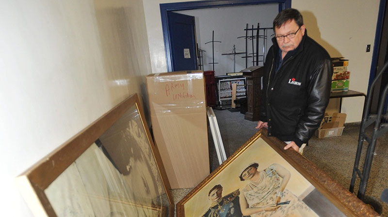 Legion president Terry Duncan looks at old paintings at the first legion branch in Canada, located in Regina, on Thursday, Jan. 3, 2013. (Roy Antal / THE CANADIAN PRESS)