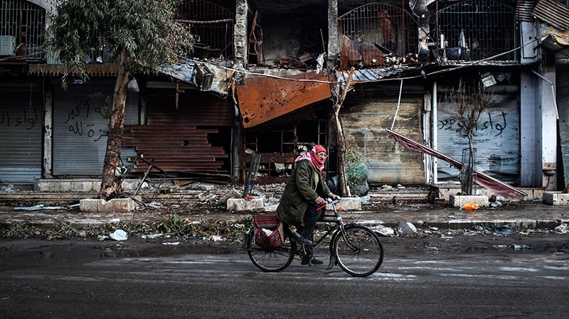 A Syrian man rides his bicycle past damaged buildings due to shelling in the old city of Aleppo, Syria, Sunday, Jan. 6, 2013. (AP / Andoni Lubaki)
