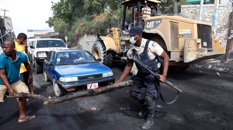 A Haitian police officer helps clear debris as a barricade is dismantled Friday, December 10, 2010, in Port-au-Prince, following a few days of rioting after the release of the election results. (Paul Chiasson / THE CANADIAN PRESS)