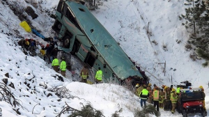 Emergency personnel respond to the scene of a multiple-fatality accident after a tour bus careened through a guardrail and fell several hundred feet down a steep embankment, near Pendleton, Ore., Sunday, Dec. 30, 2012.  (East Oregonian / Tim Trainor)