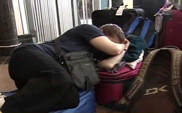 A stranded passenger, one of many, tries to get some sleep at Pierre Elliott Trudeau International Airport in Montreal on Monday, March, 10, 2008.