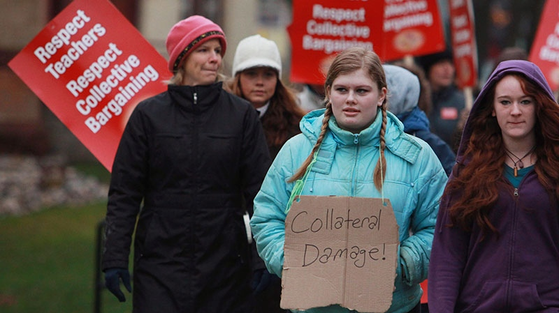 Students Alex Bradhagen and Stephanie Moses walk against both the teachers and the provincial government, claiming to be collateral damage in the dispute, as teachers from the Avon Maitland school district carry picket signs at Stratford Central School in Stratford, Ont., Monday, Dec. 10, 2012. (Dave Chidley / THE CANADIAN PRESS)