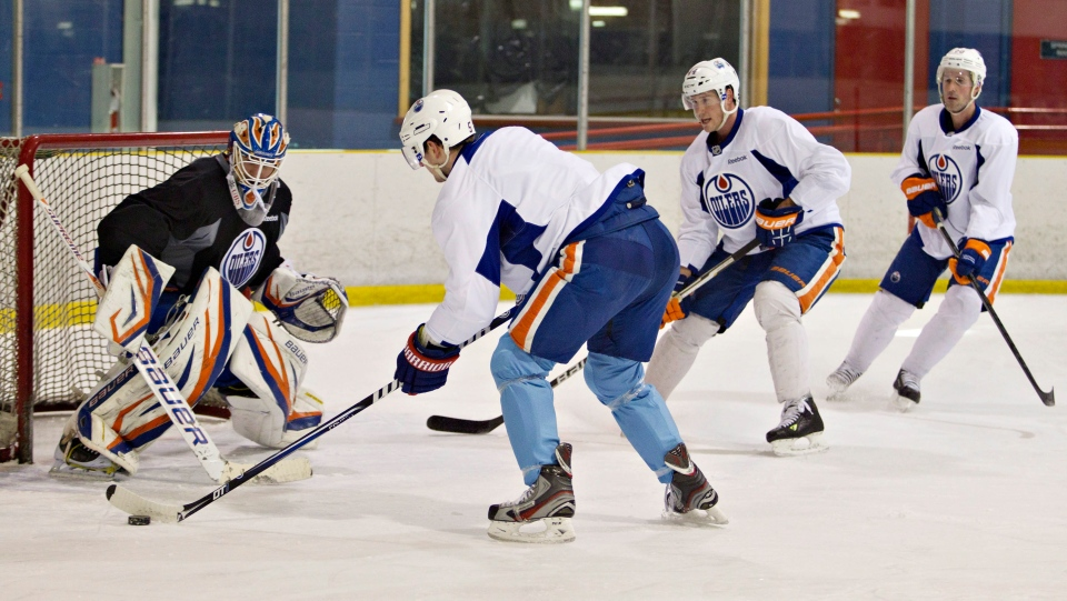 Edmonton Oilers goalie Devan Dubnyk makes a save on Ladislav Smid, left, as Corey Potter and Eric Belanger look for the rebound during the Oilers' first practice after the NHL lockout, in Edmonton, Alta., on Monday Jan., 7, 2013. (Jason Franson / THE CANADIAN PRESS)