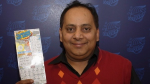This undated photo provided by the Illinois Lottery shows Urooj Khan, 46, of Chicago's West Rogers Park neighborhood, posing with a winning lottery ticket. The Cook County medical examiner said Monday, Jan. 7, 2013, that Khan was fatally poisoned with cyanide July 20, 2012, a day after he collected nearly $425,000 in lottery winnings.